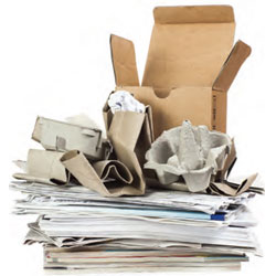 A stack of recyclable paper products including cardboard boxes and newspaper.