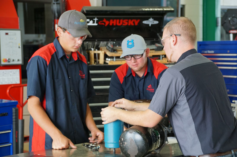 Diesel instructor working with two students