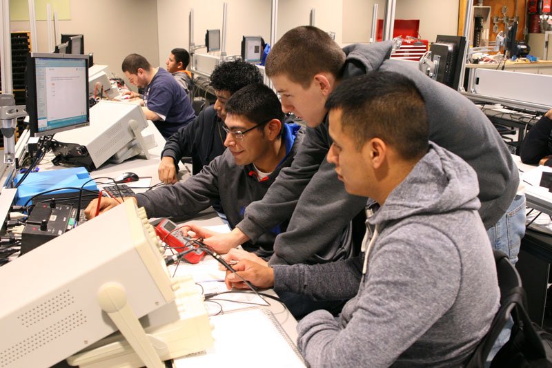 group of mechatronics students gathered around mechatronics equipment