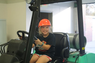 girl sitting in fork lift