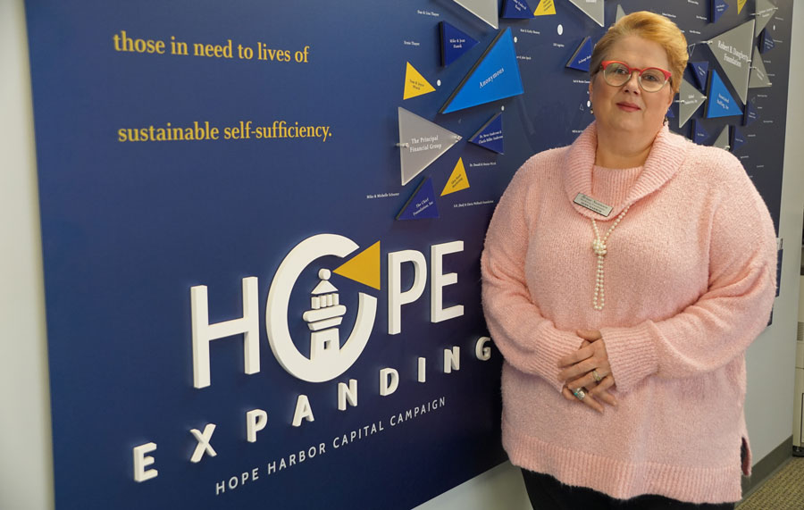 Renae Swanson in front of Hope Harbor sign