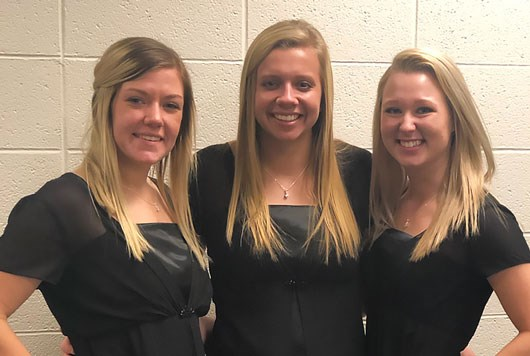 Three female students wearing black choir dresses